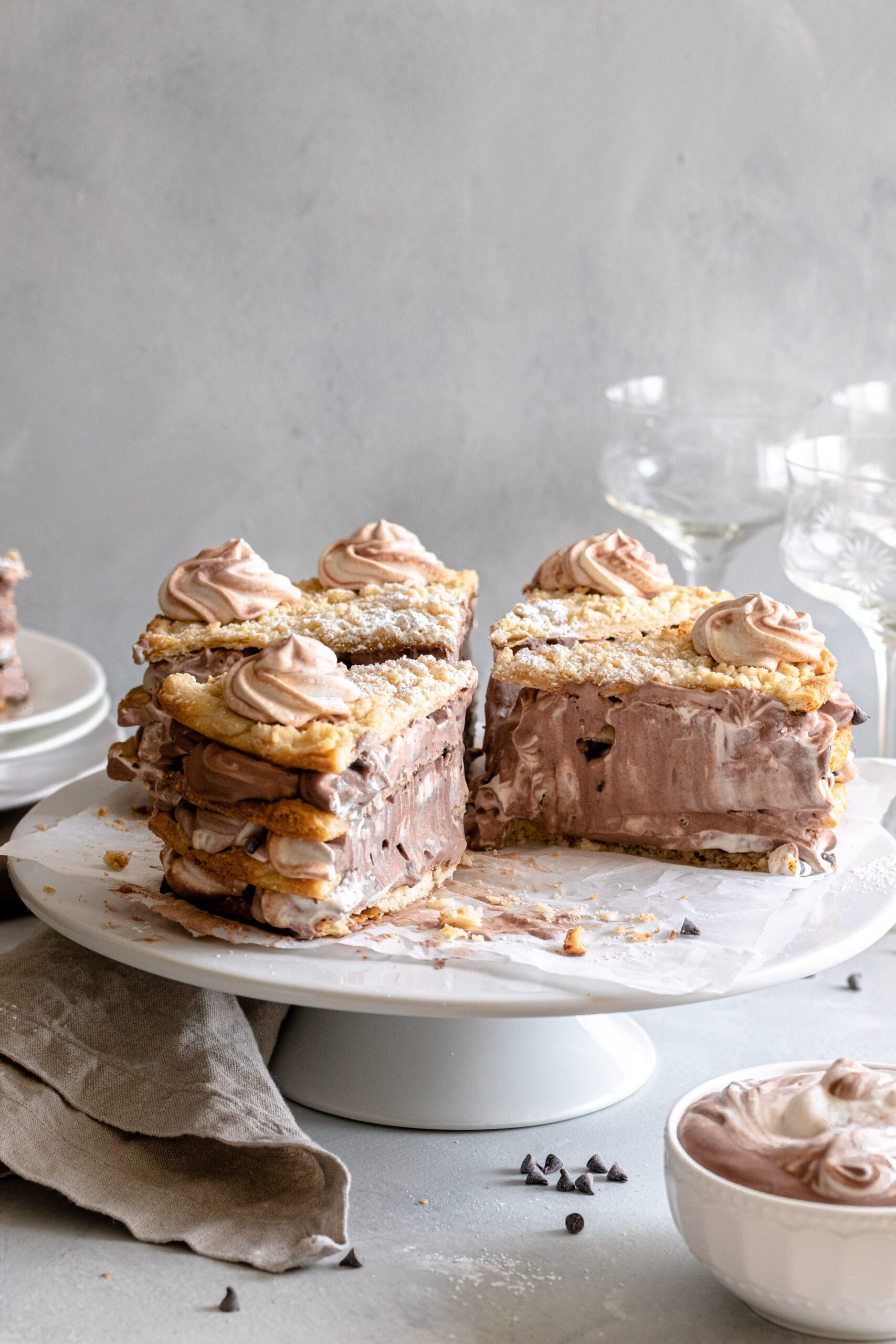 Image of layered Blättertorte Cake with marbled chocolate and plain whipped cream.