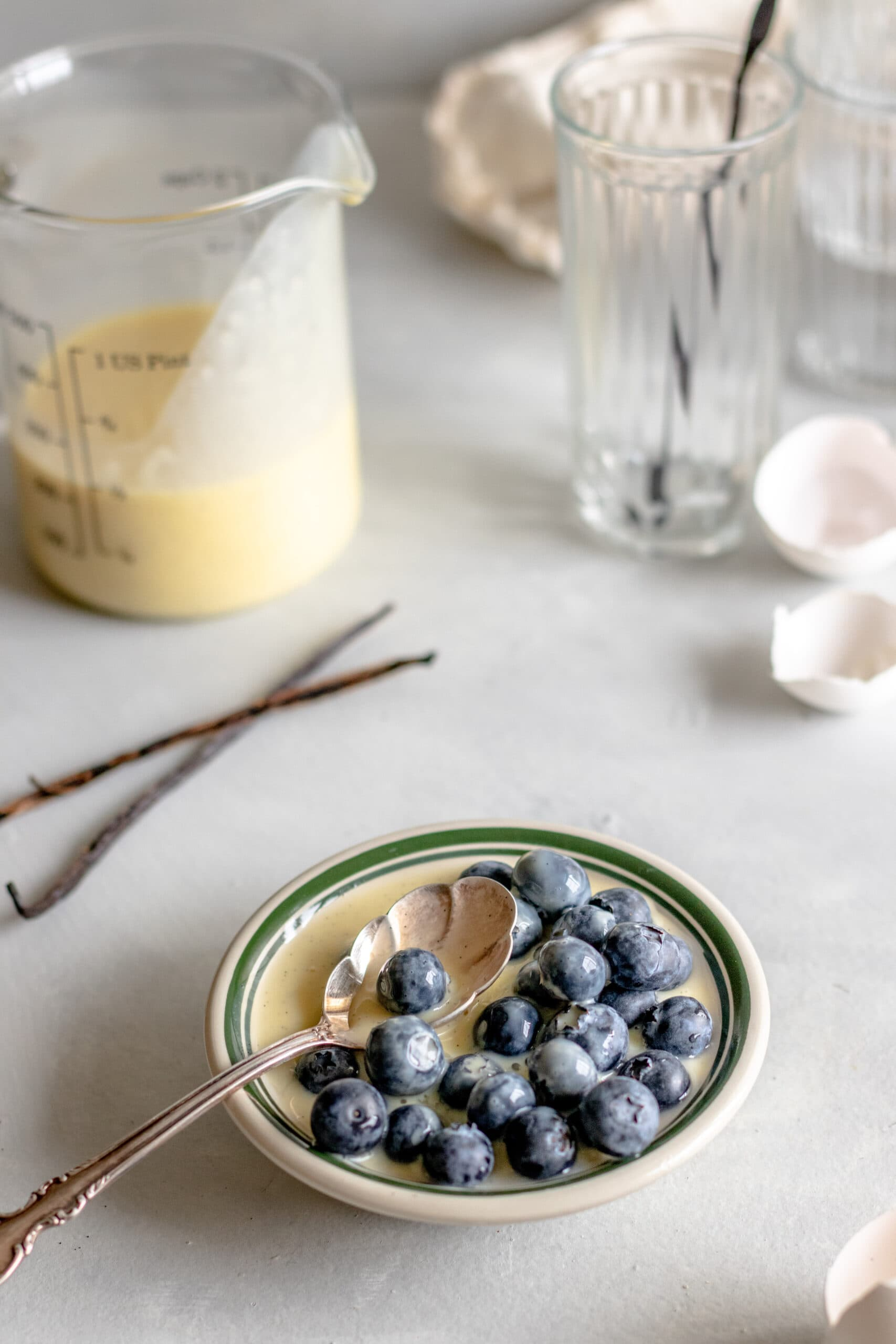 Image of vanilla custard sauce in a bowl with blueberries