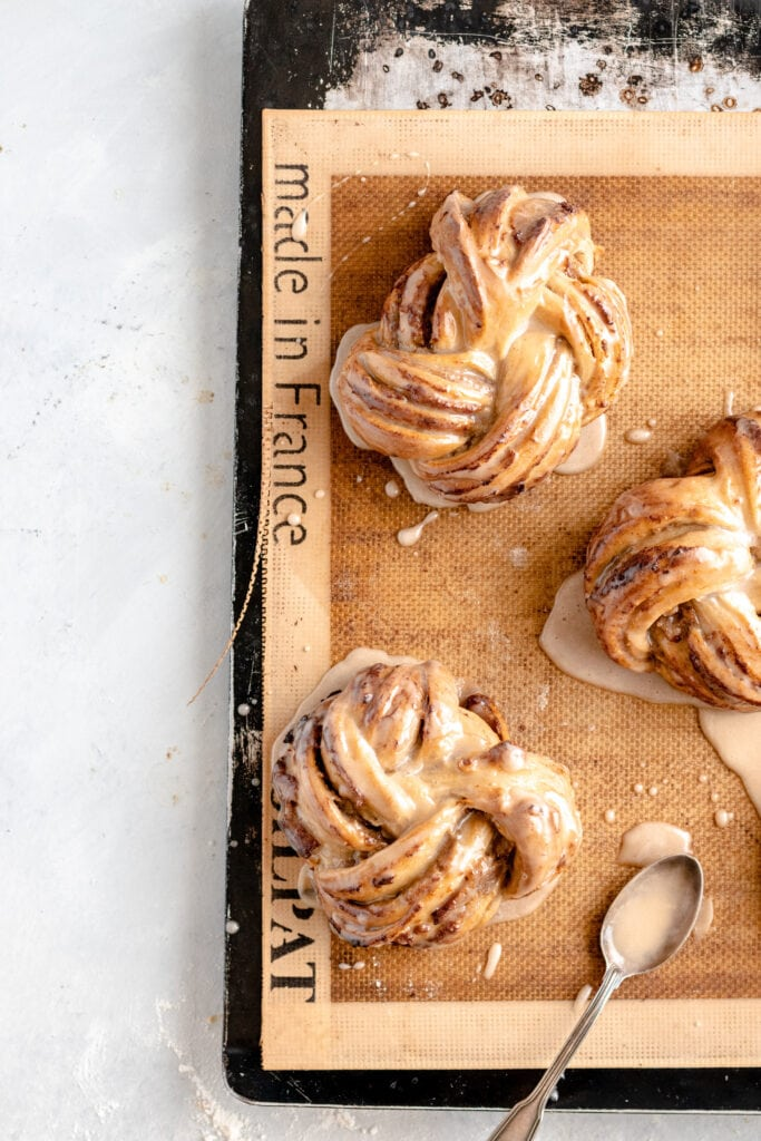 Image of freshly glazed espresso date knots/buns that have just been baked on a silicone baking mat on a baking sheet.