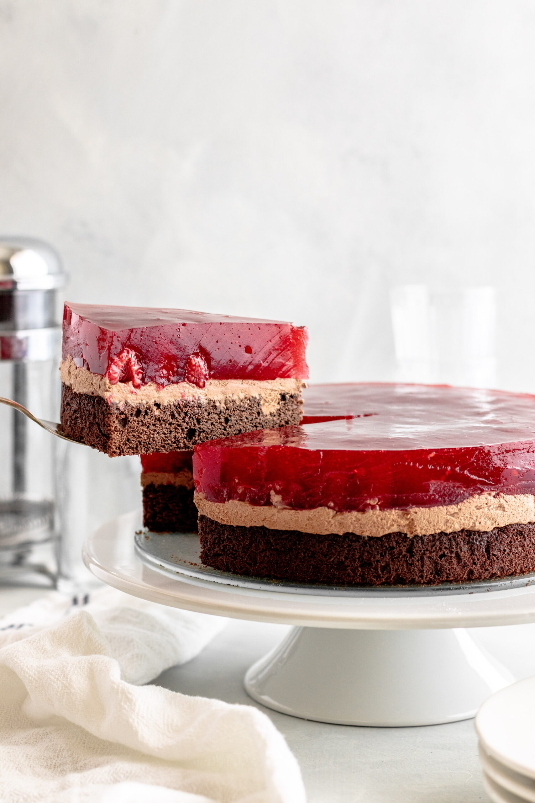 Image of layered Chocolate Raspberry Cake on a white cake stand with a slice being removed.