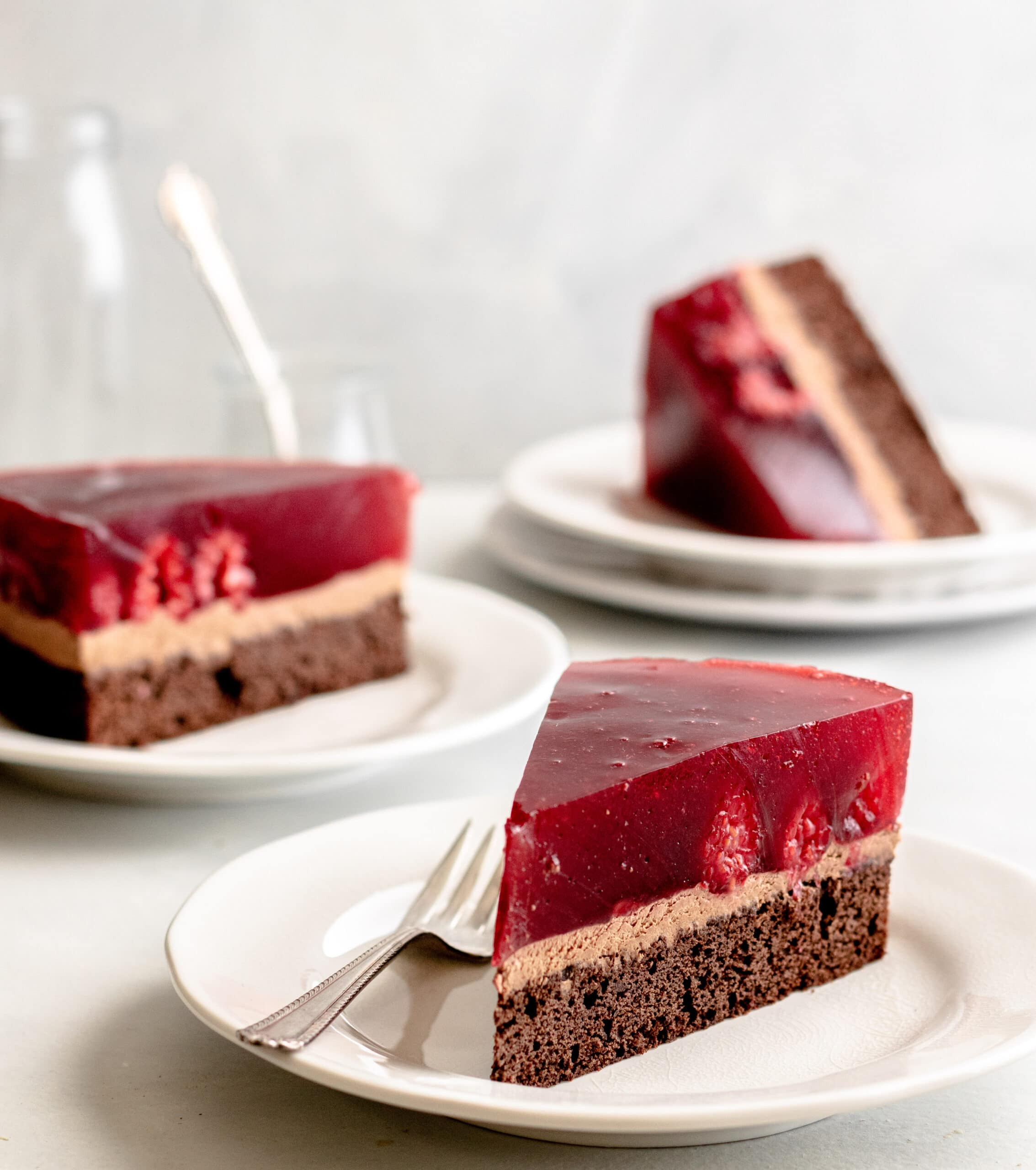 Image of chocolate raspberry cake slices on a white plate.