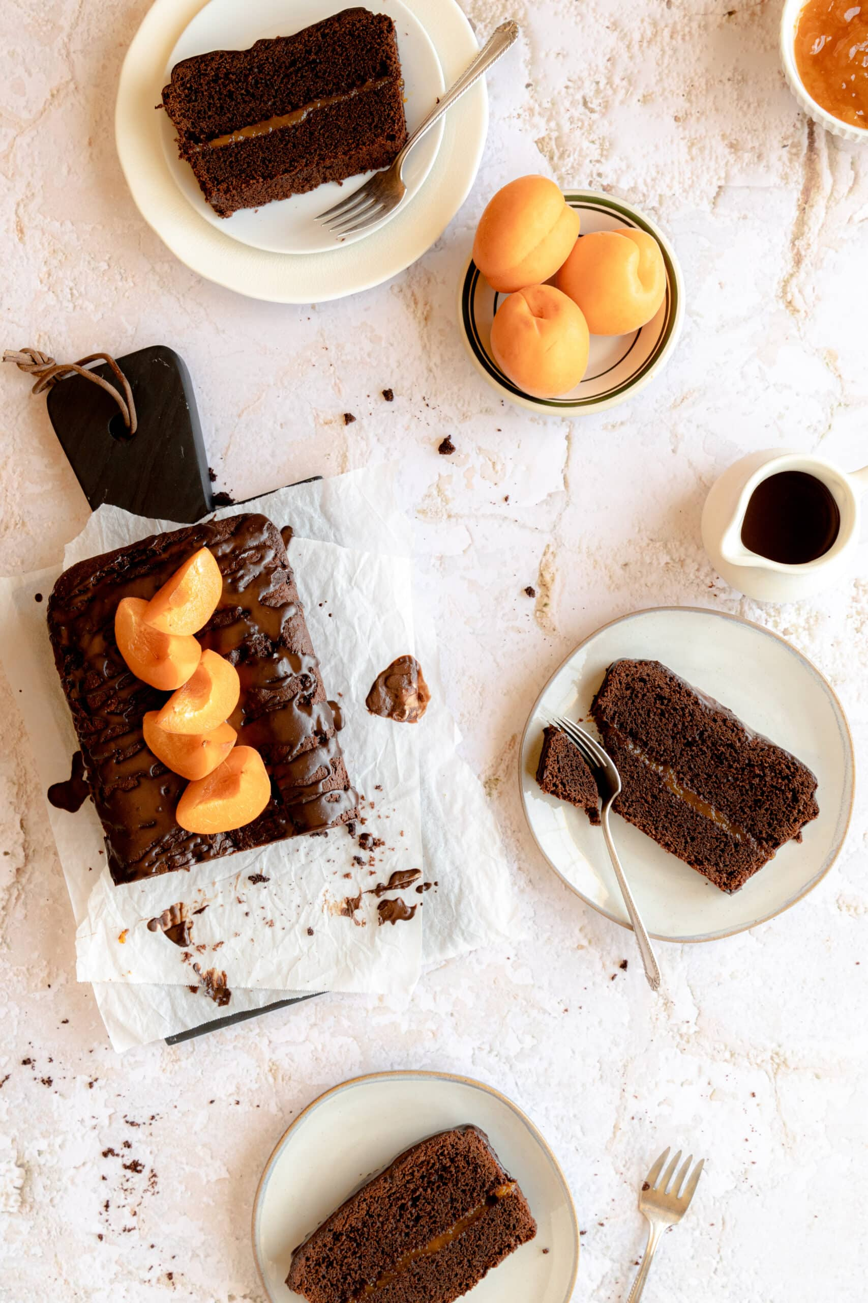 Image of Sachertorte Loaf cut into with three slices on three different white plates and crumbs strewn about.