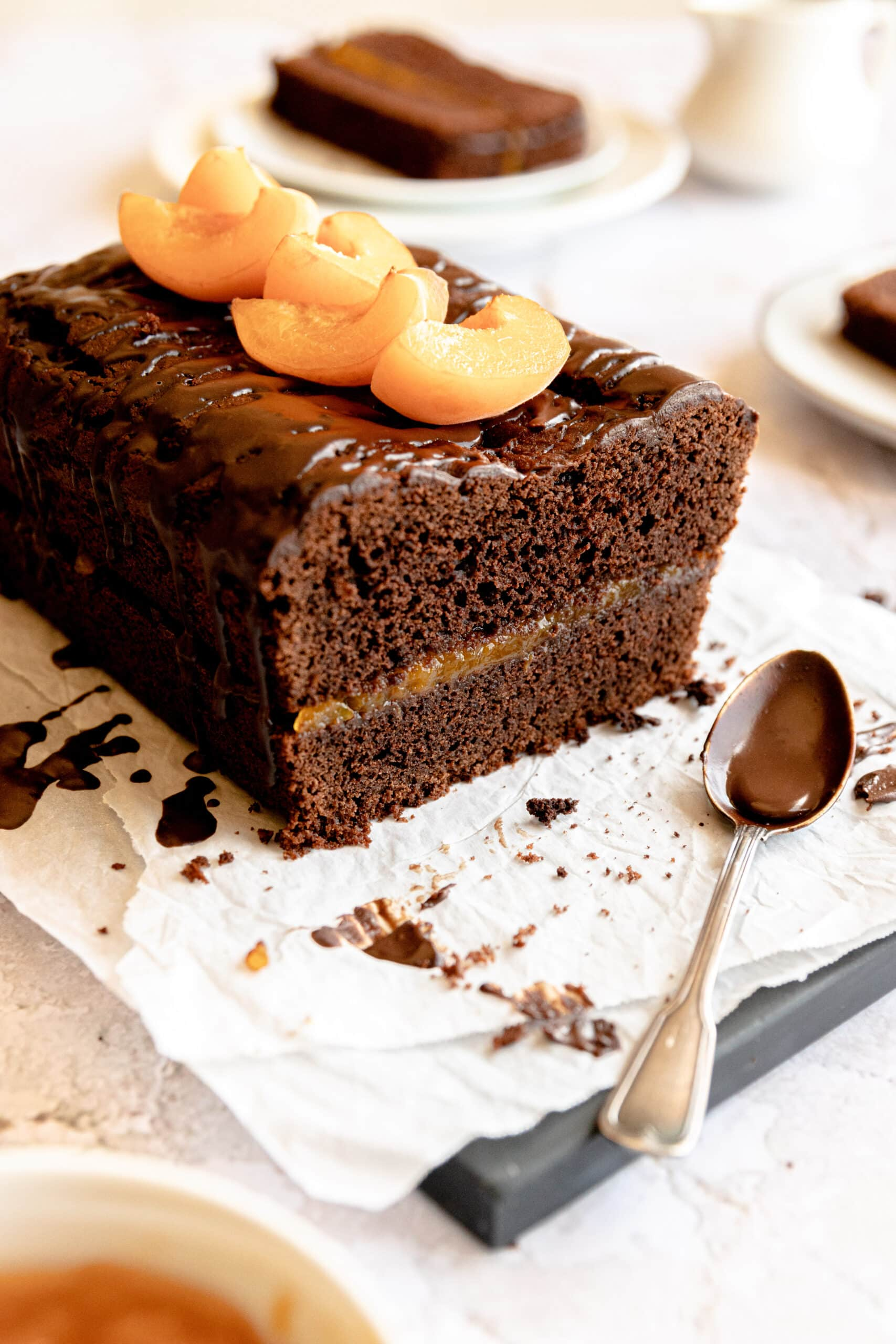 Image of the sachertorte loaf cut into that is split and layered with apricot jam and topped with fresh apricots.