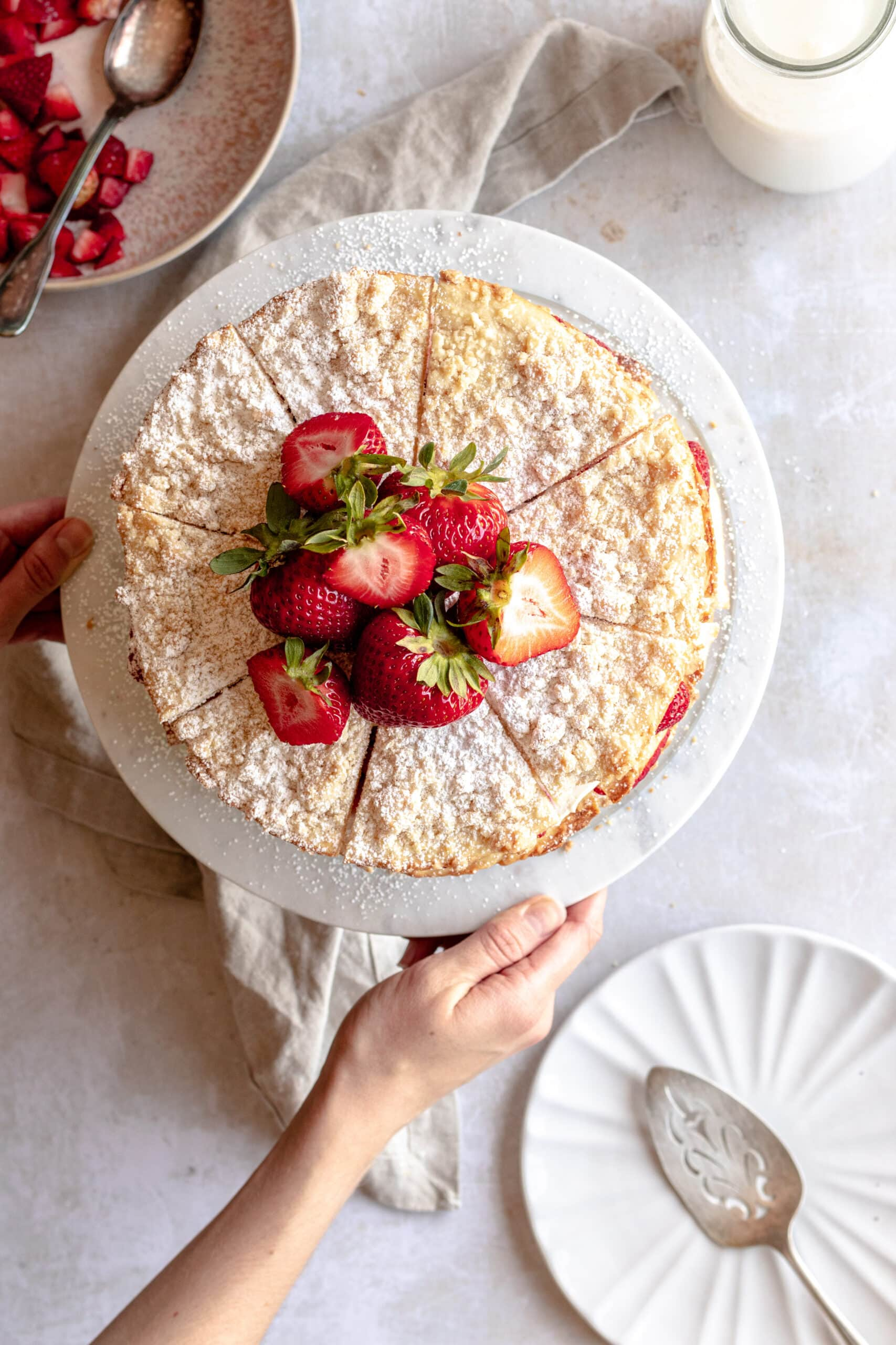 Overhead image of the Strawberry Blättertorte with hands reaching into the scene setting the cake stand on the surface.