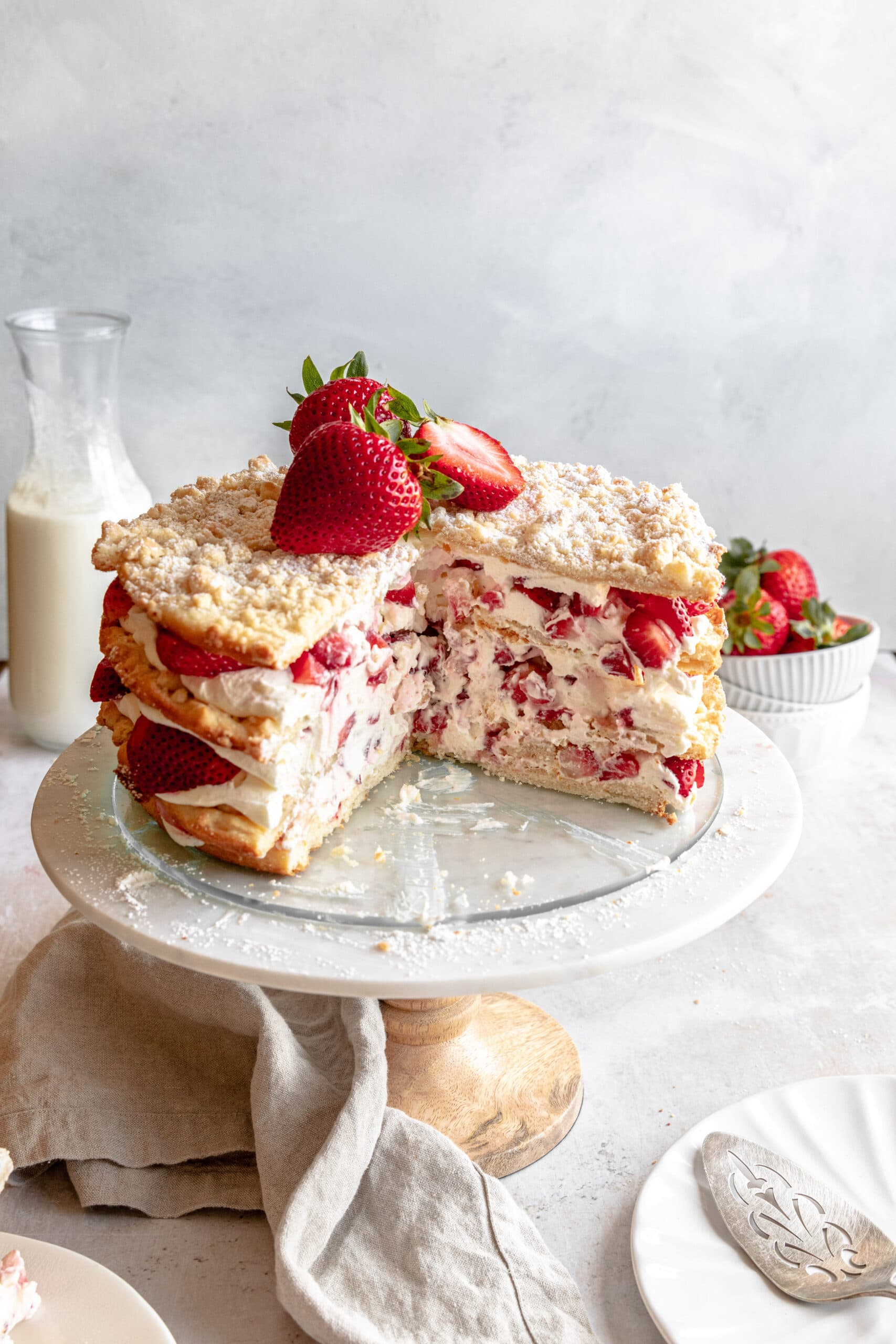 Image of the Strawberries and Cream layered cake cut into on a white cake stand.