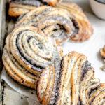 Image of lemon poppyseed layered, swirled buns on a grey and black baking sheet.