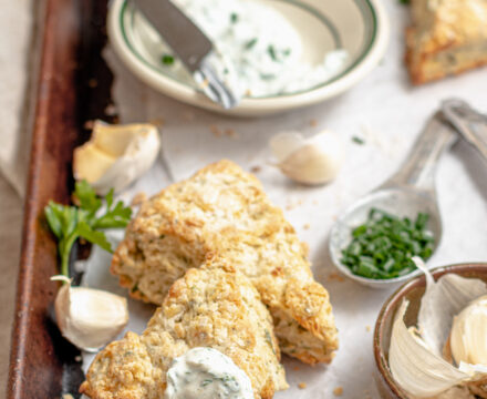 Image of herbed scones with extra kräuter quark dip on a baking sheet with parchment paper.
