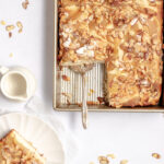 Image of almond pear butterkuchen with one slice cut out from a 9x13 pan and almonds strewn about.
