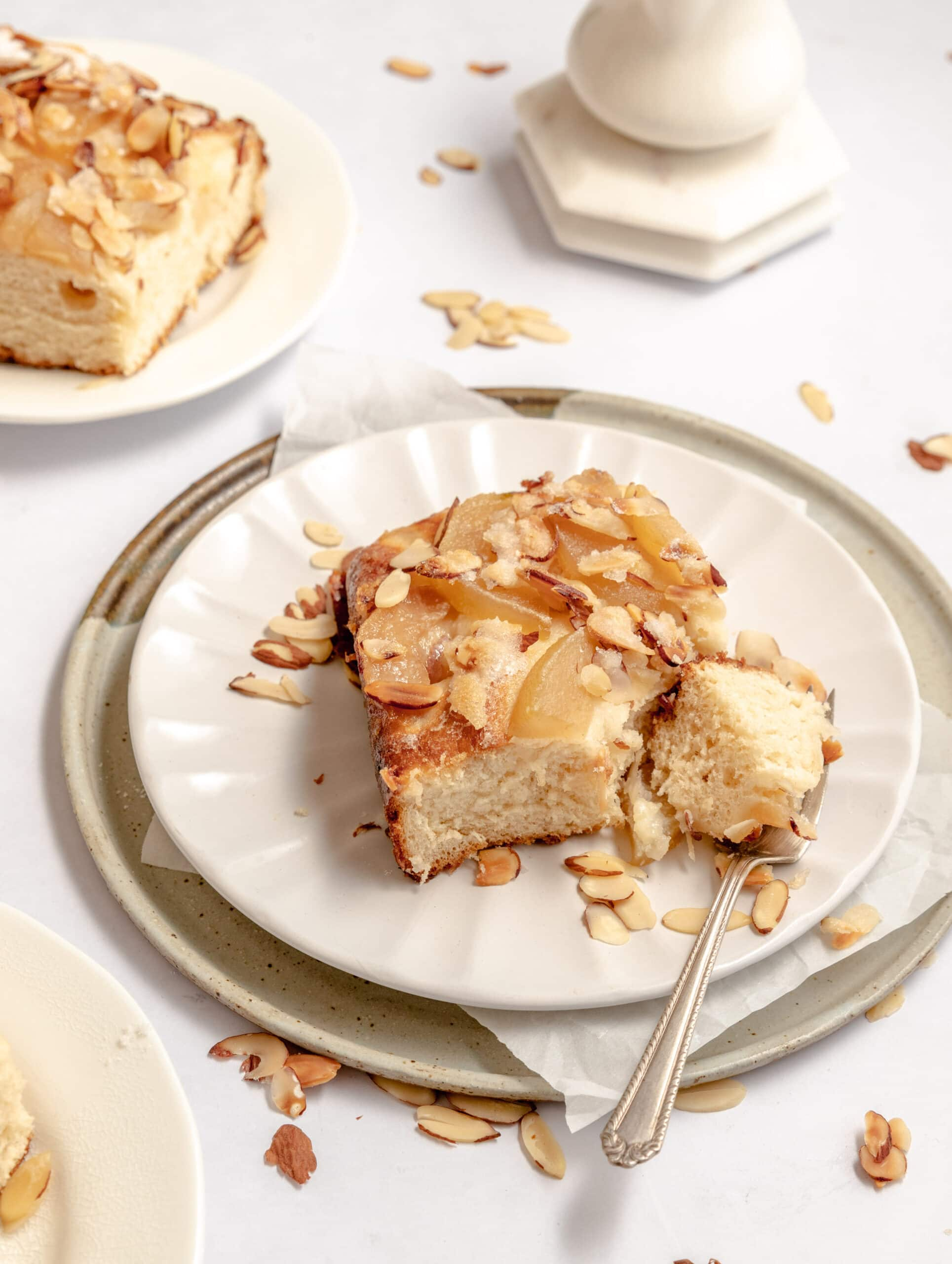 Close up image of a slice of the almond pear butterkuchen on a stack of two plates with extra sliced almonds laying around.