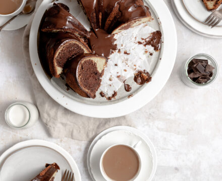 Image of marmorkuchen - german marble bunt cake that is swirled chocolate and vanilla batter- sitting on a white cake stand with chocolate ganache glaze and coffee cups sitting around