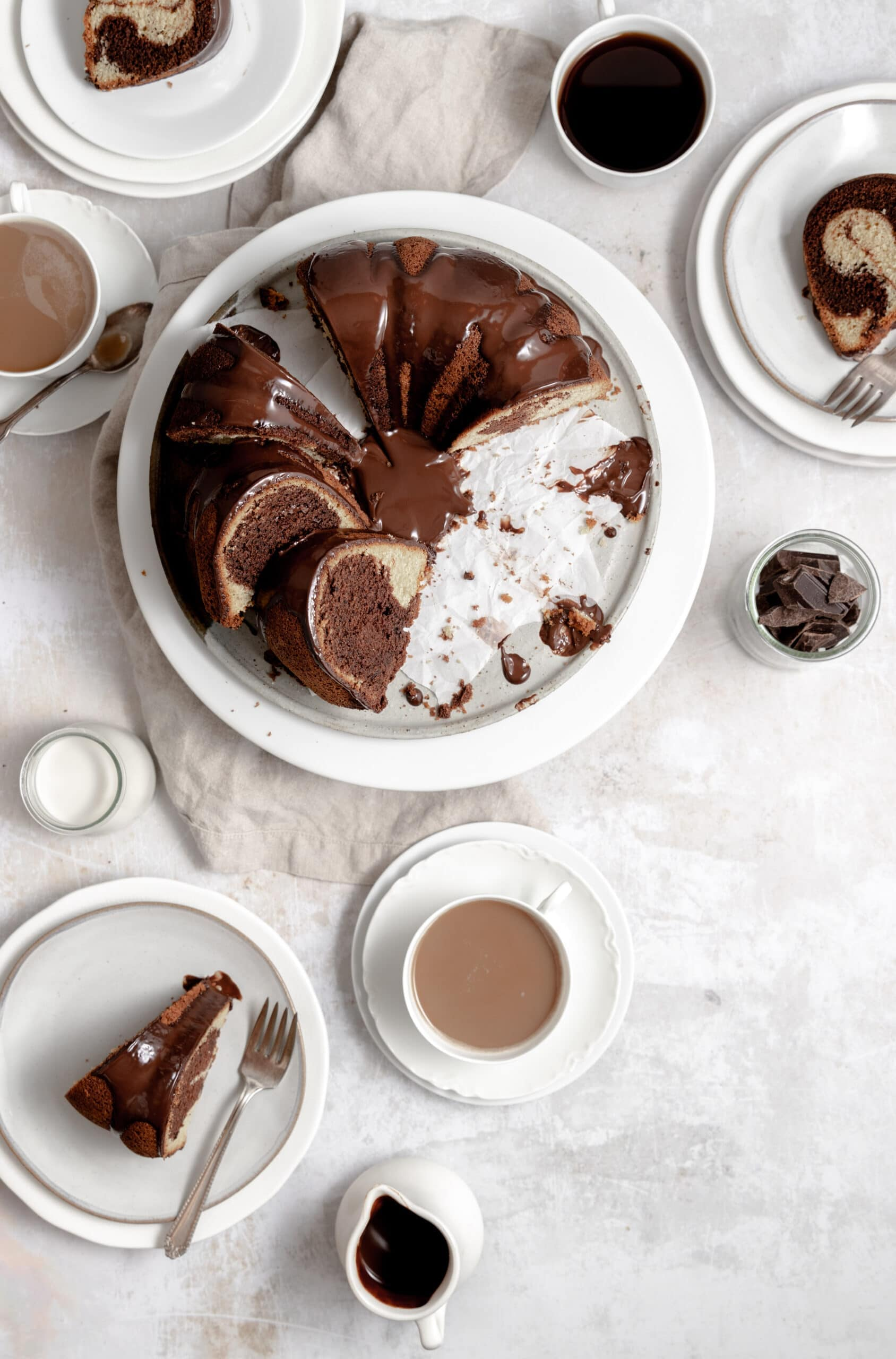 Image of marmorkuchen - german marble bunt cake that is swirled chocolate and vanilla batter- sitting on a white cake stand with chocolate ganache glaze and coffee cups sitting around.ddd