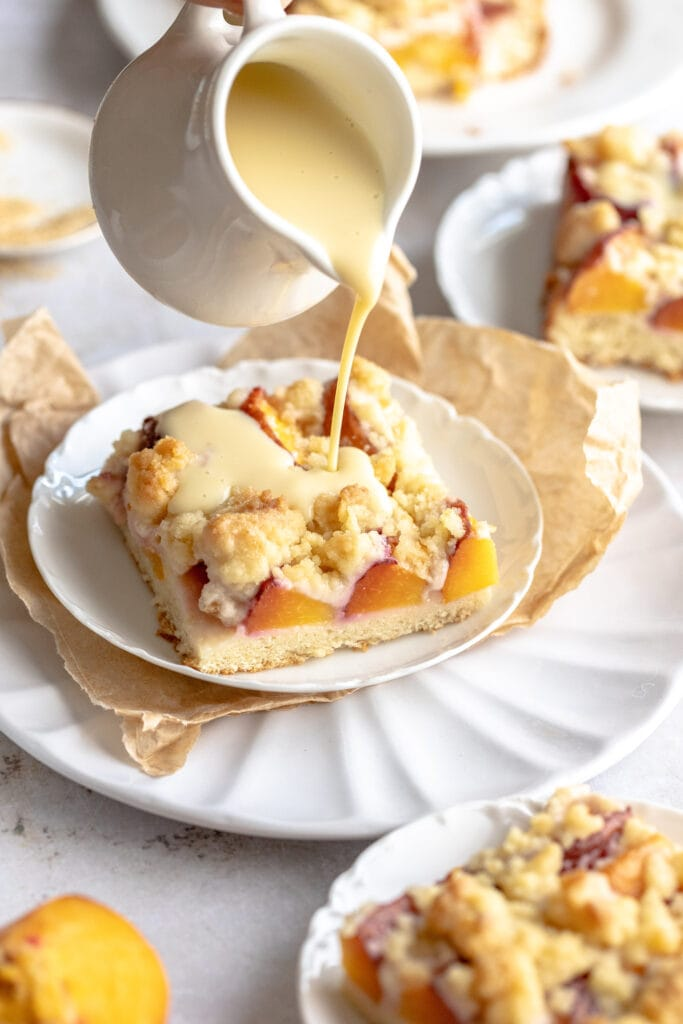 Pfirsichkuchen mit streusel (peach streusel cake) cut into large squares on a white plate with vanilla sauce being drizzled overtop.