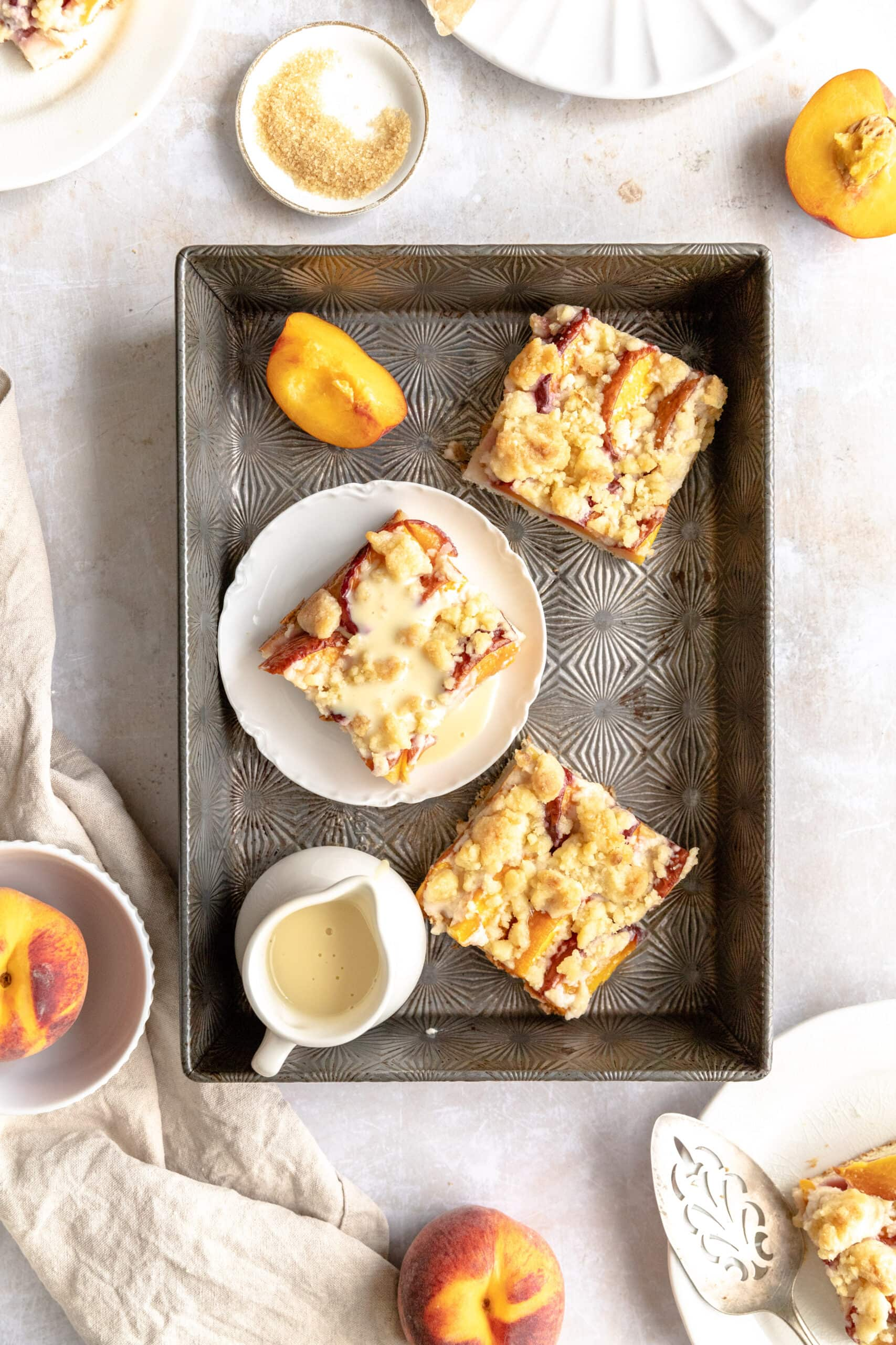 Pfirsichkuchen mit streusel cut into squares in a 9x13 baking pan with vanille soße and extra peaches.