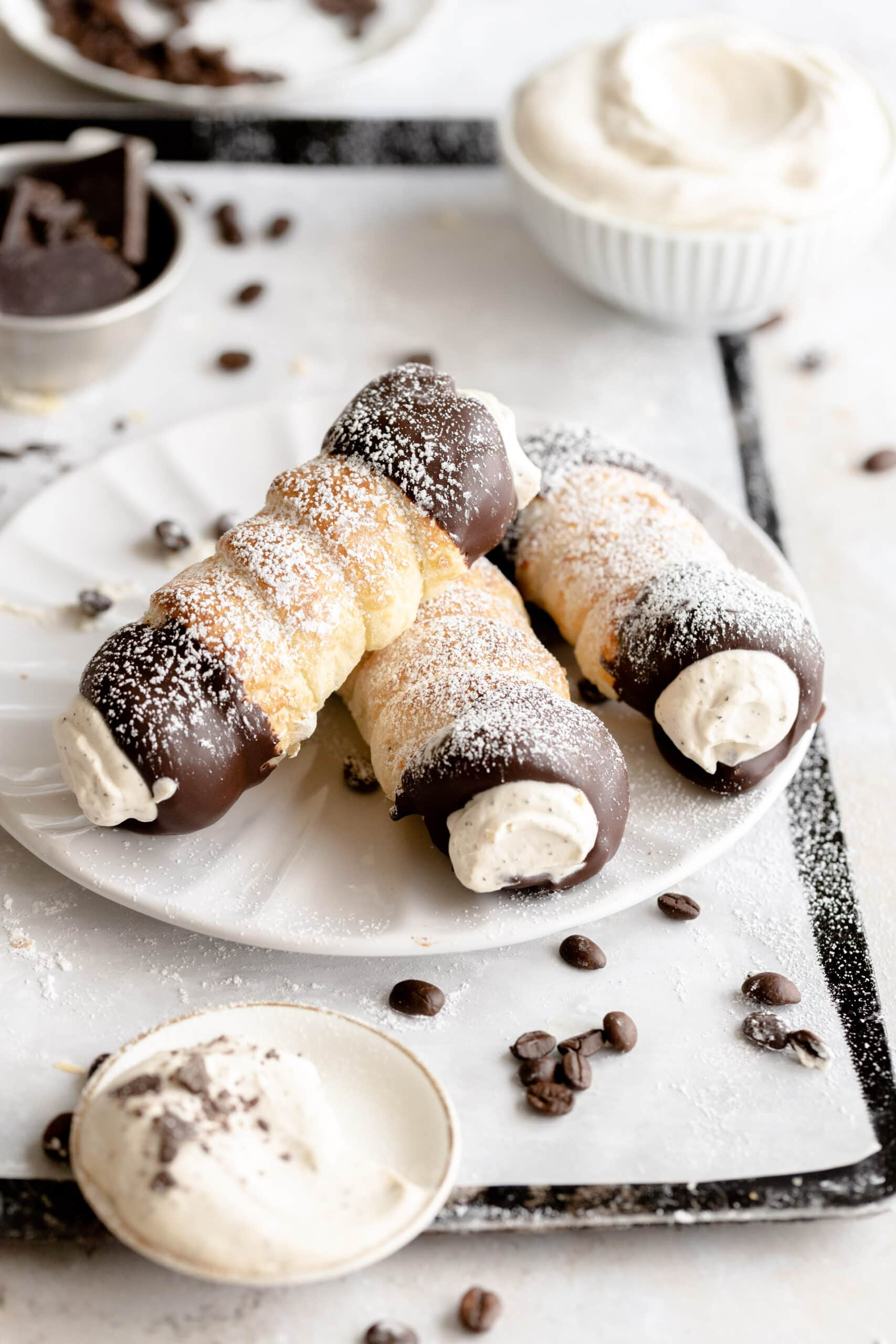 Three schaumrolle dusted with powdered sugar laid out on a white plate.