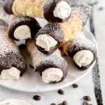 Puff pastry rolls filled with coffee whipped cream and dipped in chocolate stacked on a white plate and dusted with powdered sugar.