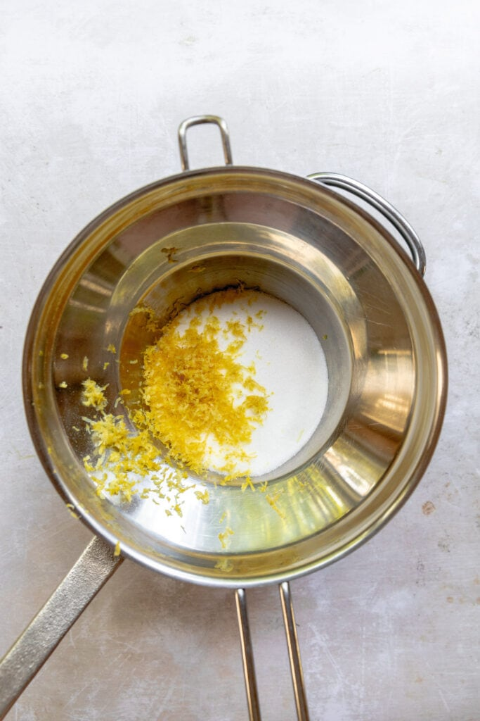 Sugar, salt and lemon zest in a double boiler for Lemon Sandkuchen.