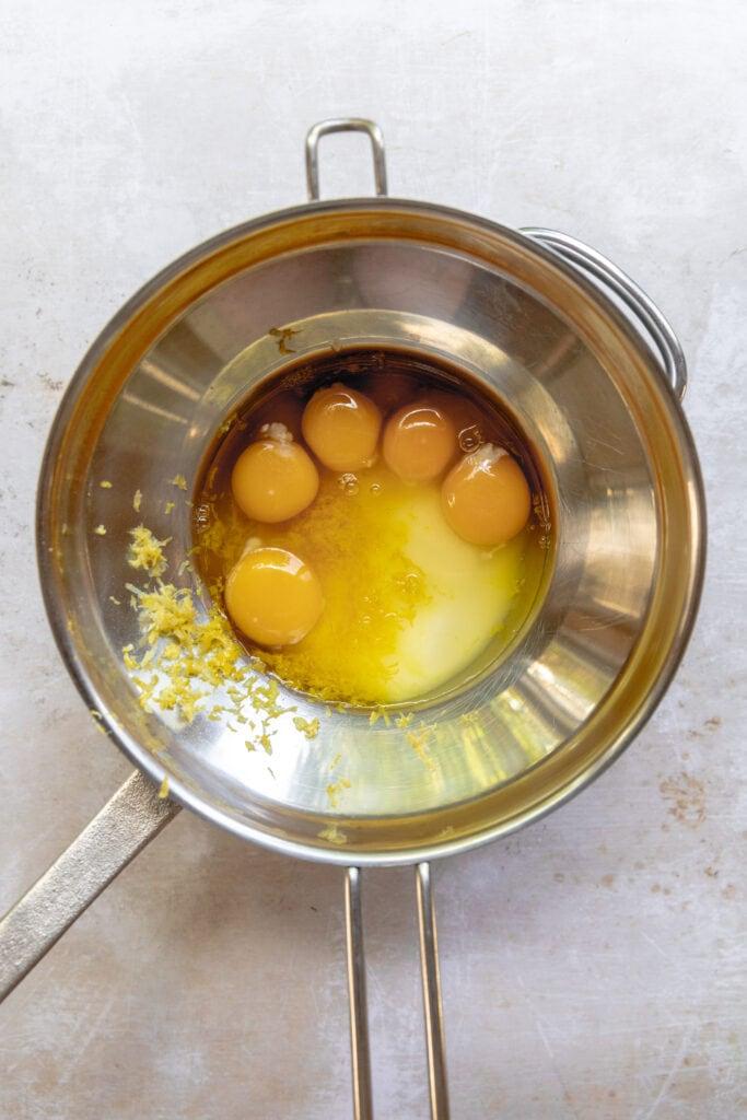 Eggs, Sugar, salt and lemon zest in a double boiler for Lemon Sandkuchen.