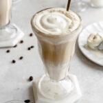 Image of German iced coffee - aka Eiskaffee - in a milkshake glass topped with whipped cream.