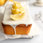 Lemon sandkuchen loaf cake on white parchment with a white lemon glaze and topped with lemon wedges