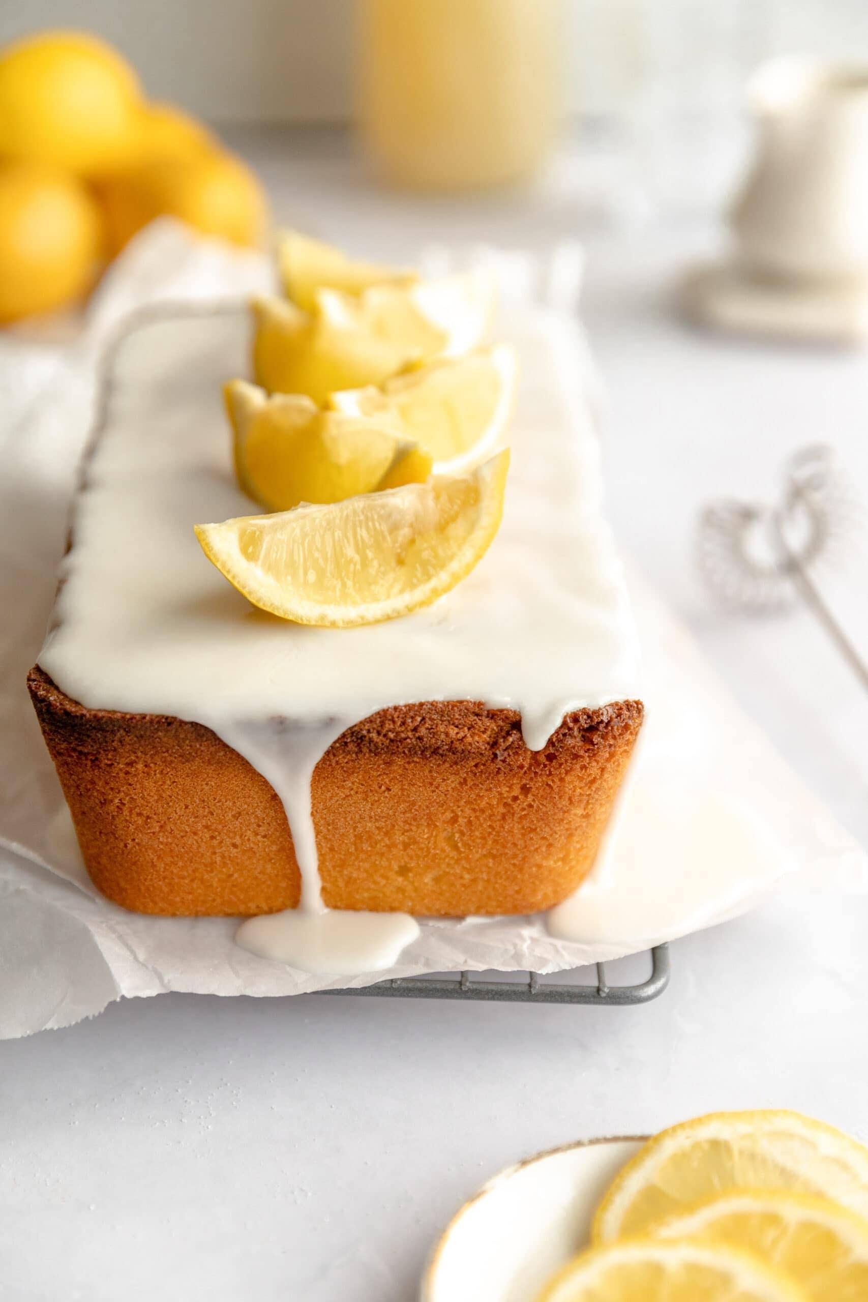 Sandkuchen (Lemon loaf cake) glazed with a lemon glaze and topped with lemon wedges.