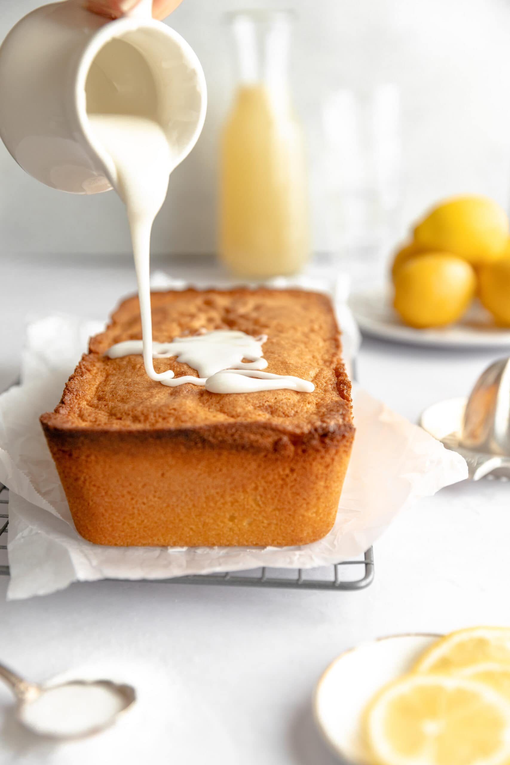 Lemon Sandkuchen Loaf on white parchment paper on a wire rack being drizzled with a lemon glaze.