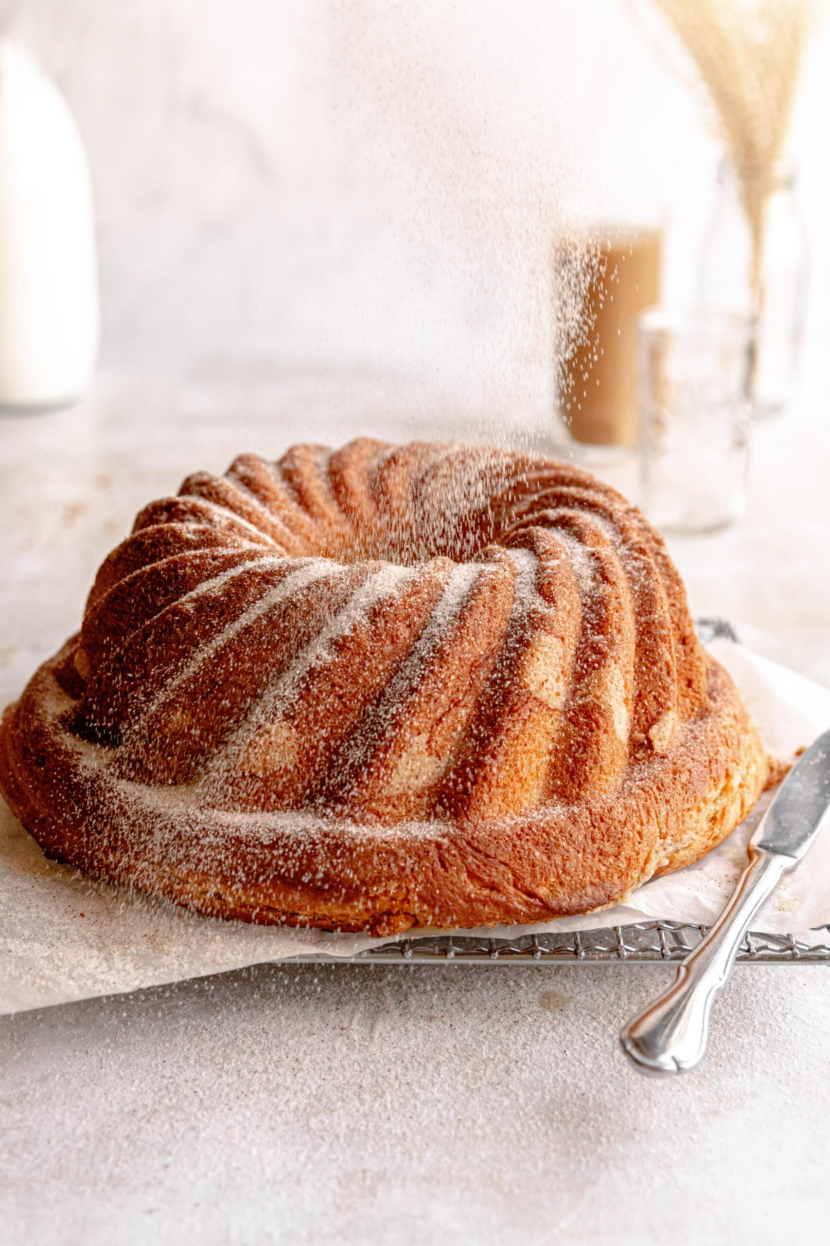 Coffee Cake Gugelhupf on a cooling rack with cinnamon sugar being poured over top.