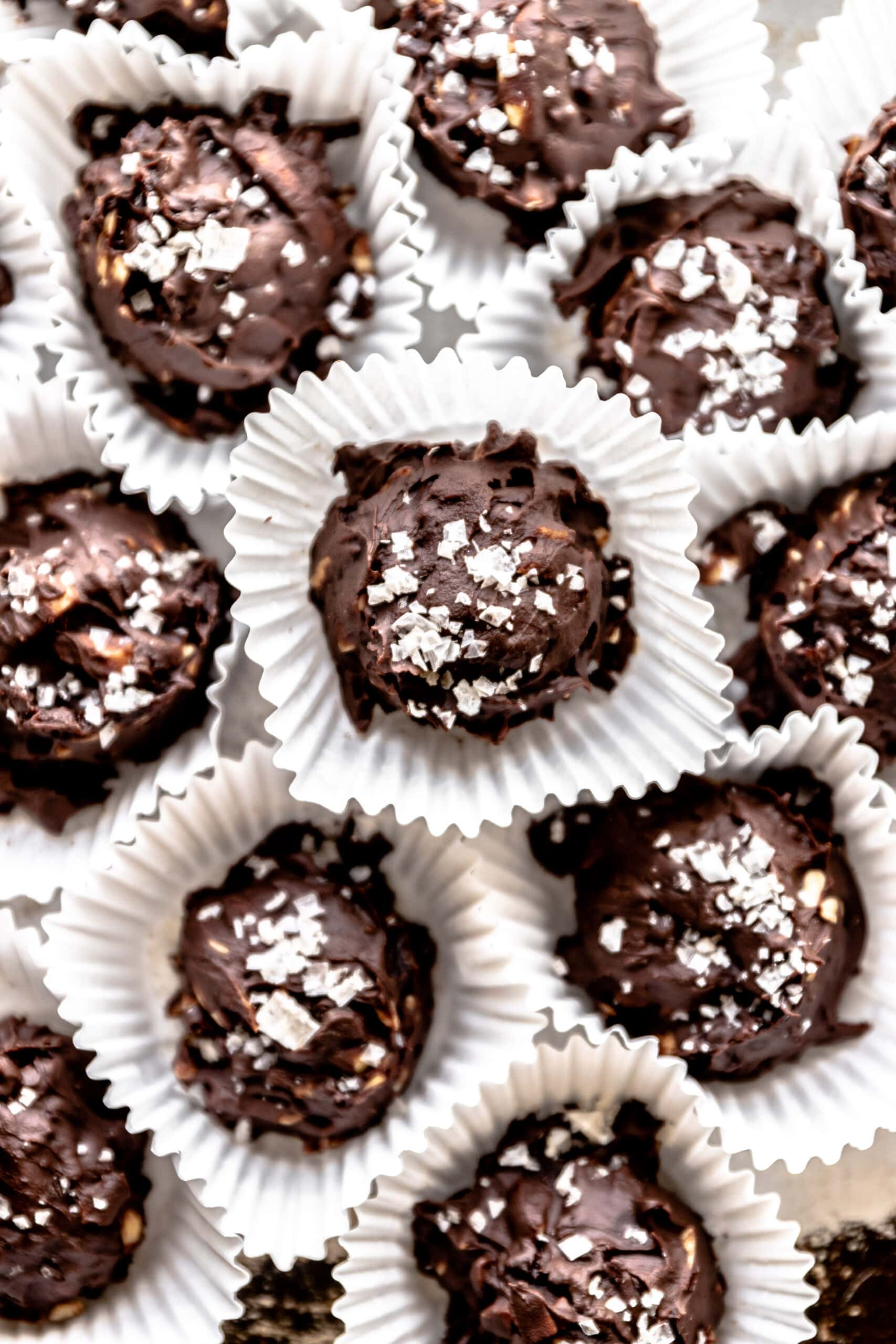 Chocolate cherry truffles with almonds and topped with sea salt in individual muffin liners.