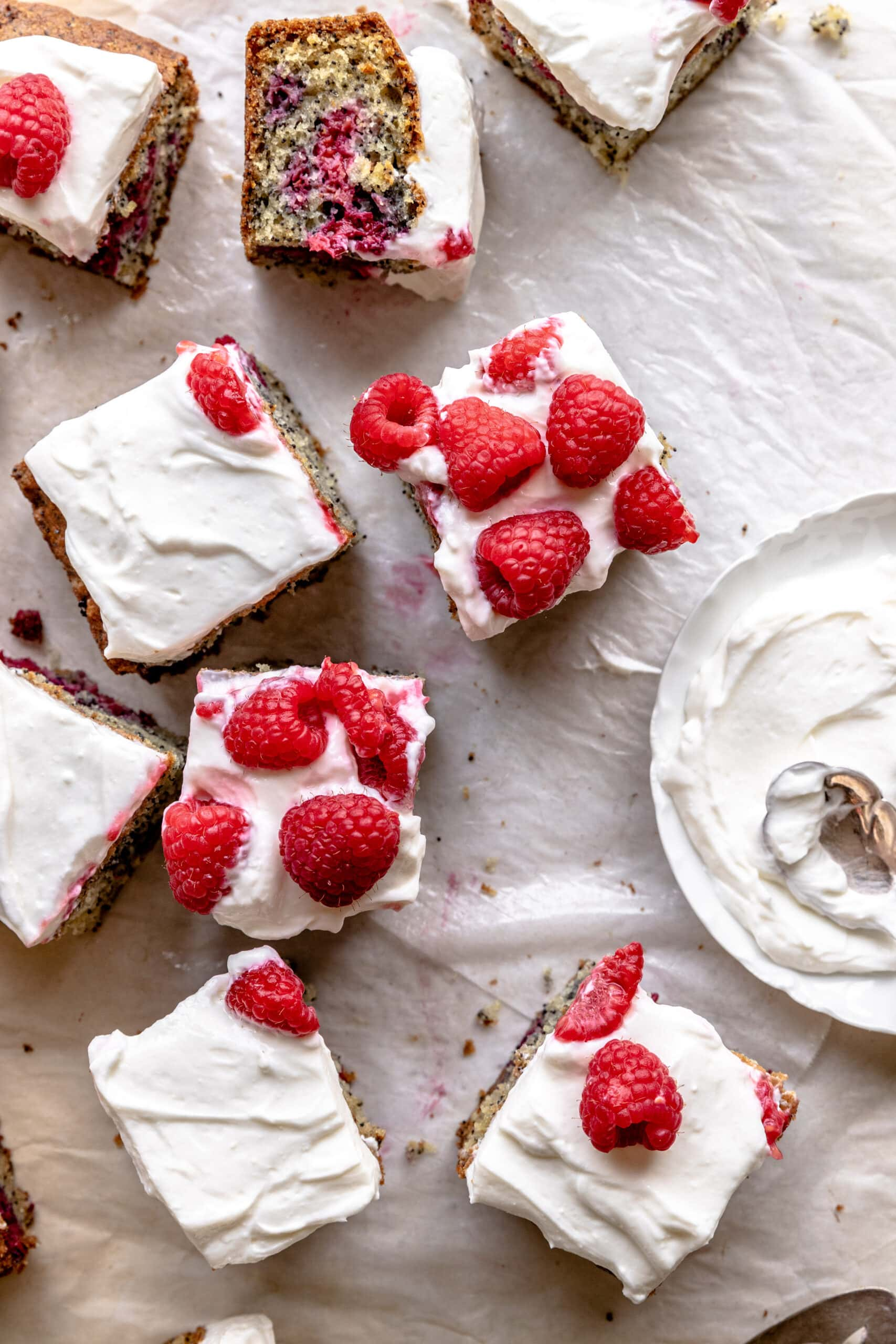 Overhead image of squares of the Raspberry Snack Cake on a few layers of parchment and topped with raspberries.