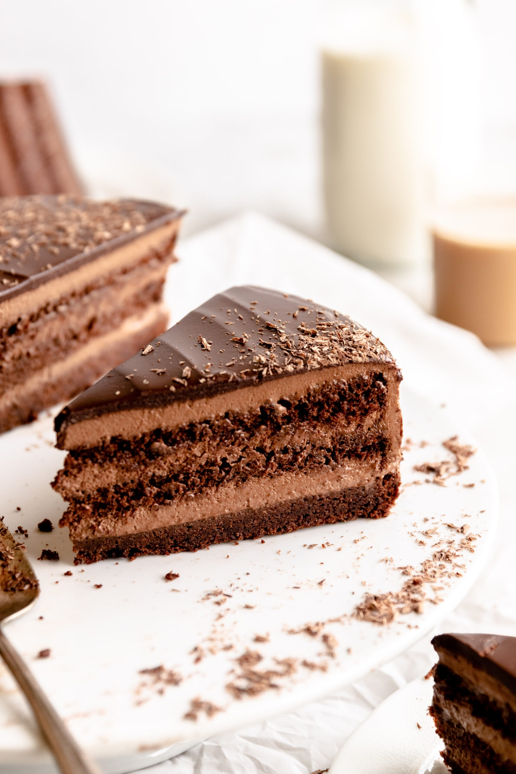 Up close image of a slice of chocolate mousse cake on a white cake stand.