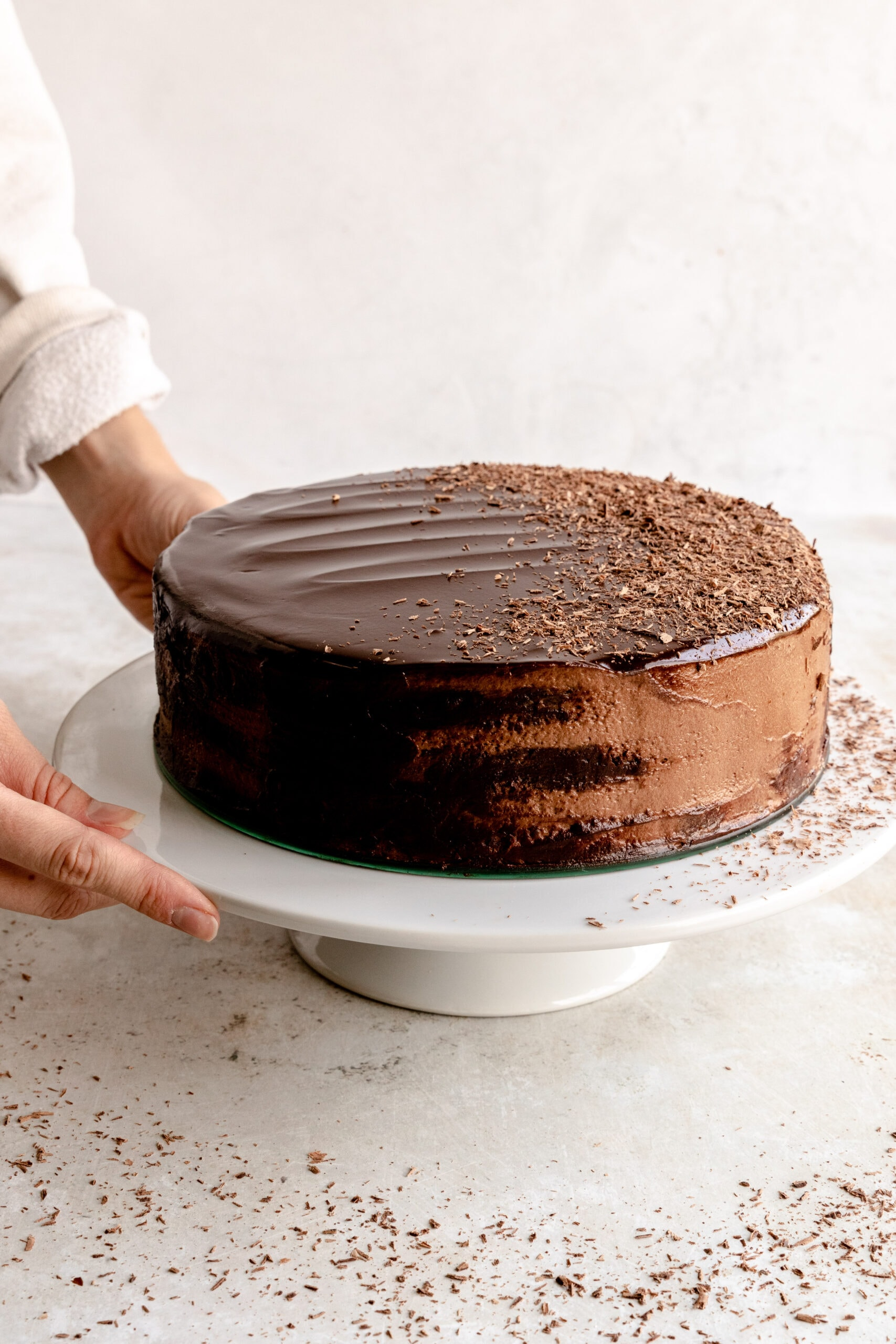 Image of hands holding a white cake stand with the chocolate mousse torte on top.