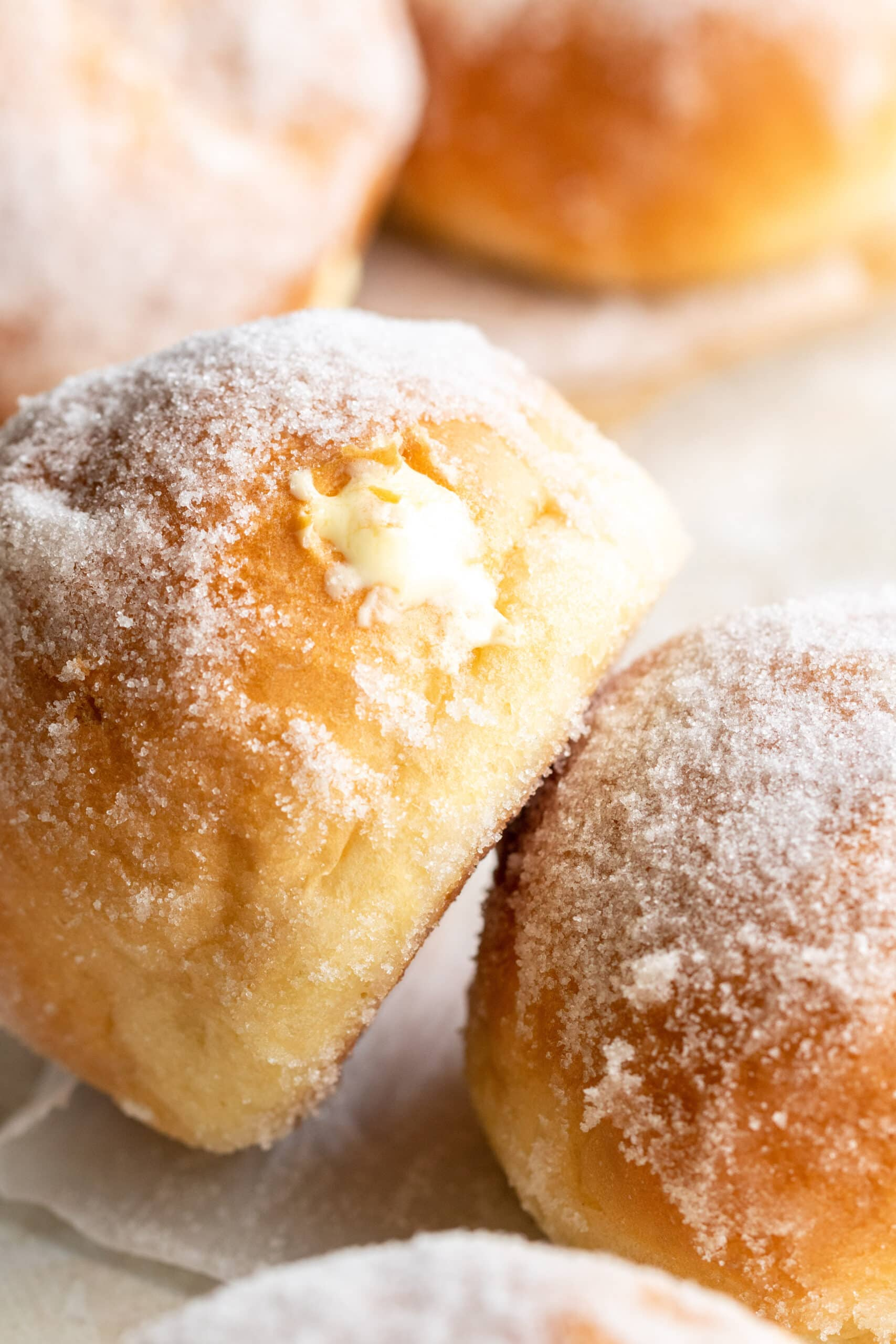 up close image of two vanillekrapfen with the hole where the vanilla cream was piped into it, showing.