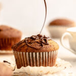 Chocolate being drizzled on top of the spiced marble cake muffin.