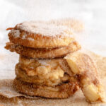 Tower of 5 Apfel ringe being showered with cinnamon sugar.