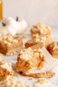 Side view of a streusel pumpkin pie bar with a bite taken out of the corner.