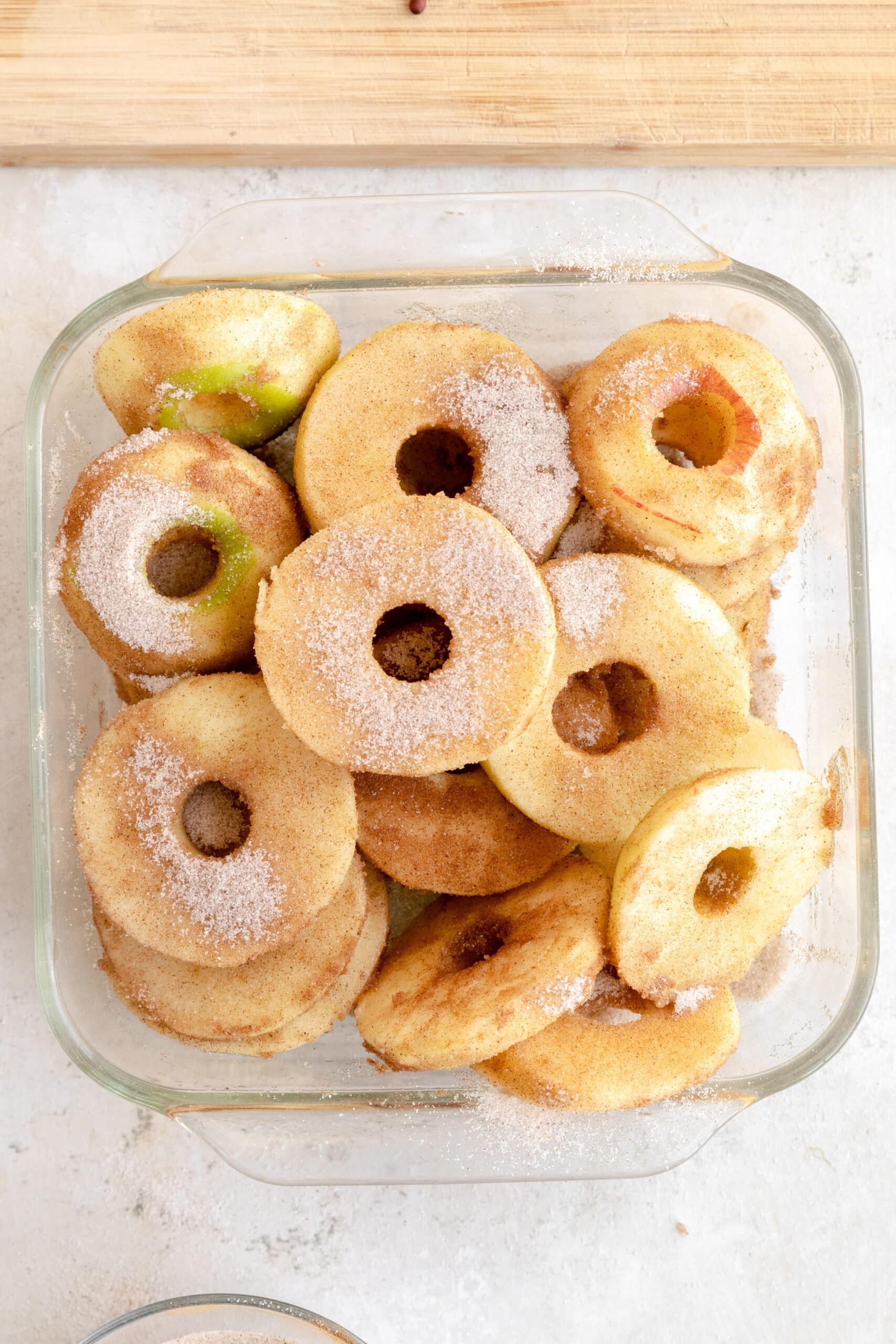 Apple slices tossed with cinnamon sugar and vanilla in a baking dish.