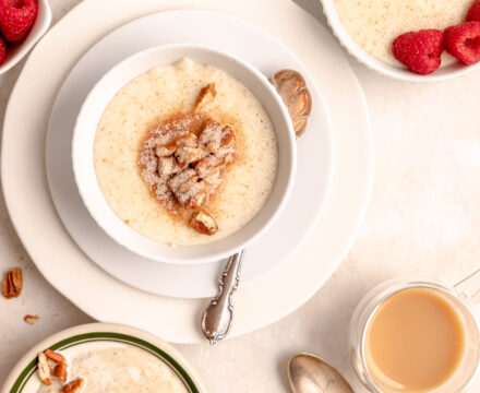 Overhead image of table with multiple bowls of Grießbrei topped with nuts, cinnamon sugar and raspberries.